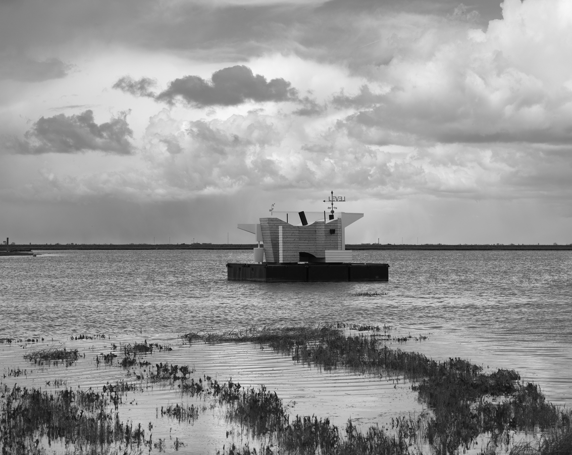 Black and white photo of Flood House on the Thames Estuary, cloudy skies